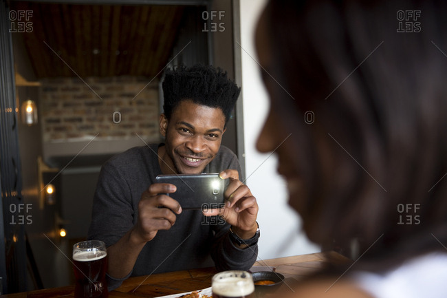 Man taking a photo of his date with a smartphone