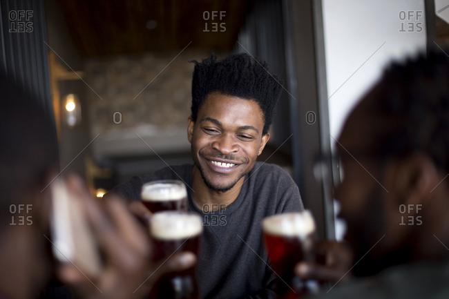 Three men toasting at a bar