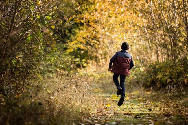 Boy skips along forest path
