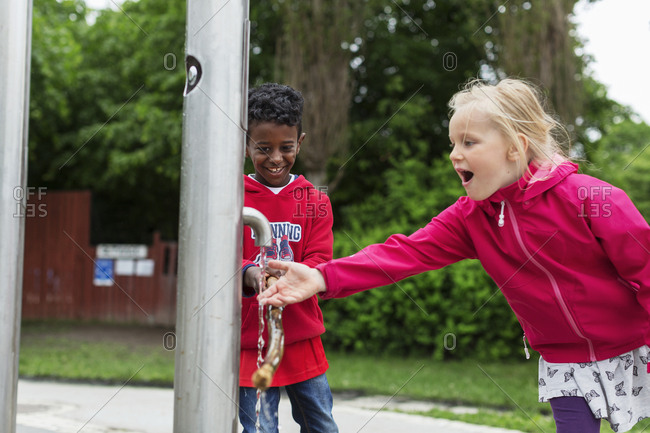 Boy and girl playing with outdoor tap