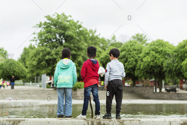 Boys standing at pond