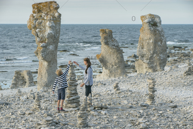 Mother and son stacking rocks on beach