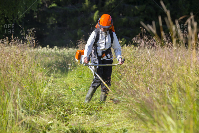 Senior woman with grass strimmer