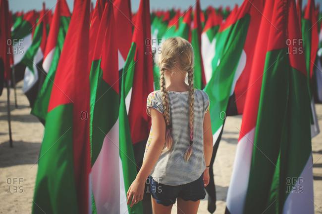 Young girl walks amid United Arab Emirates flags
