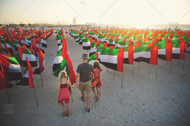 Family walks together amid flags on Kite Beach, Dubai