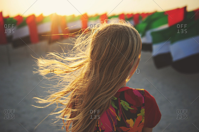 Young girl stands amid United Arab Emirates flags at sunset