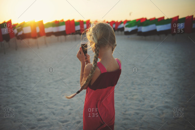 Young girl using her mobile to capture United Arab Emirates flags