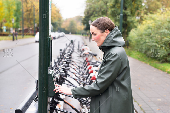 Woman using keypad to rent bicycle on city street