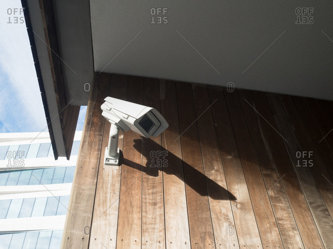 Security camera mounted on wooden wall of building