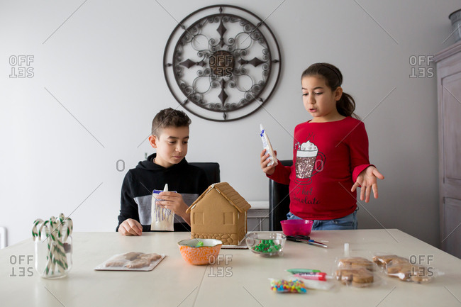Two kids planning to decorate a gingerbread house