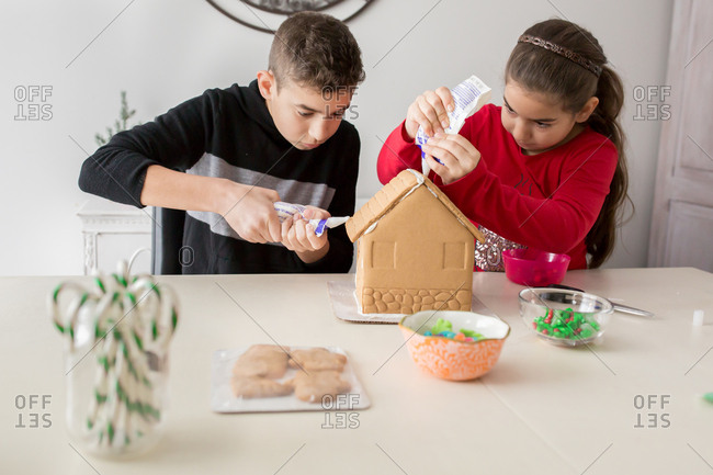 A boy and girl working on a gingerbread house