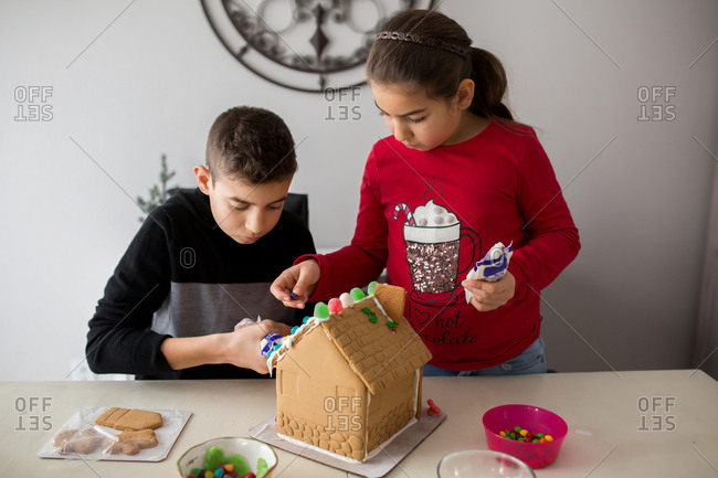 A girl and boy decorating roof of a gingerbread house