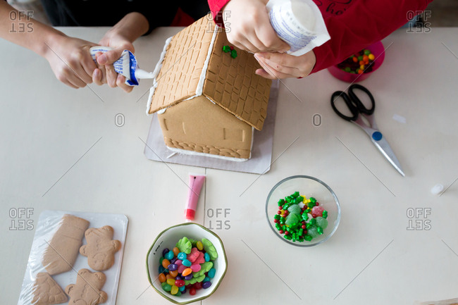 Children decorating a gingerbread house