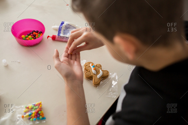 Young boy decorating a gingerbread cookie