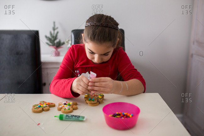 Girl decorating a gingerbread cookie