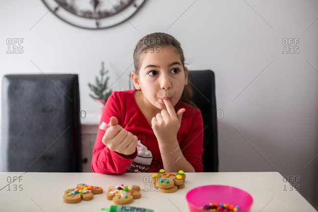 Young girl tasting frosting from a gingerbread cookie