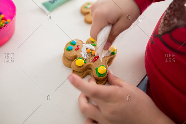 Close up of child's hand decorating a cookie
