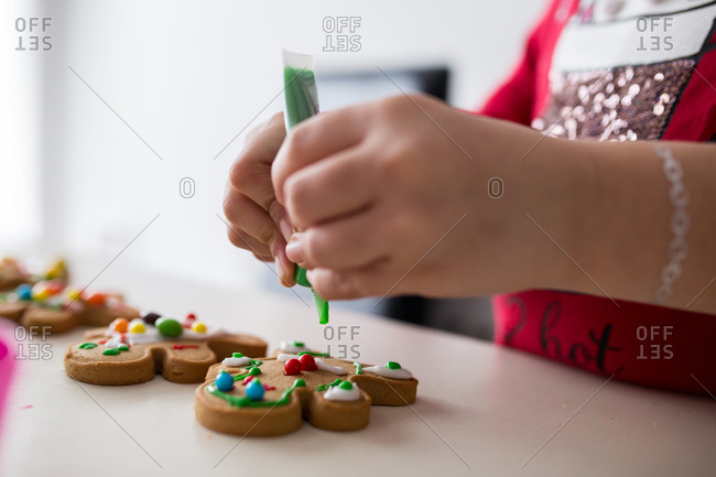 Young girl decorating a row of gingerbread cookies