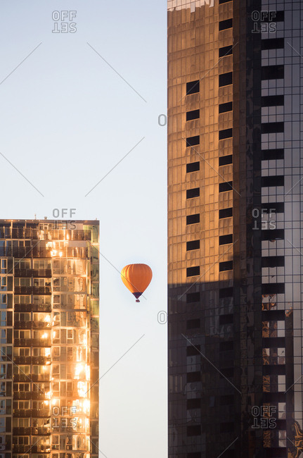 Hot air balloon seen through office buildings in early morning light