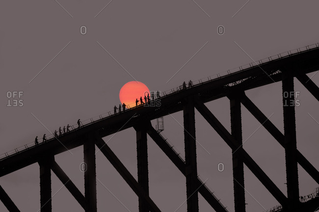 Harbour Bridge with climbers at sunset in Sydney, Australia