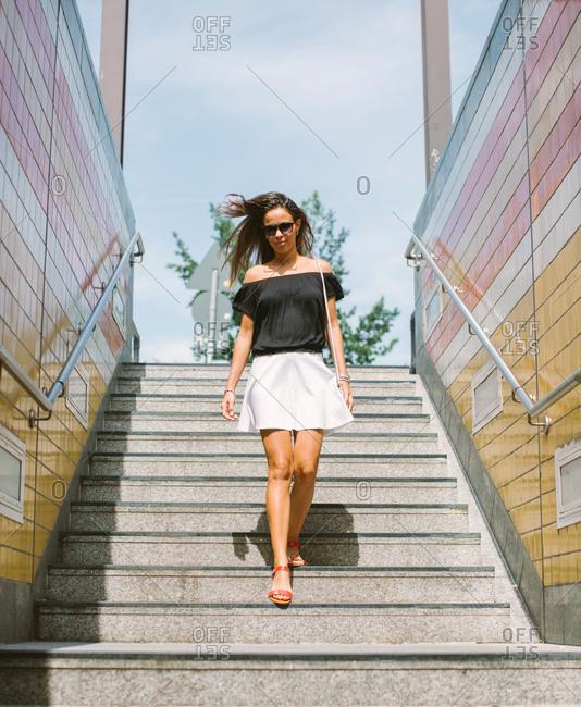 Stylish woman walking down outdoors steps