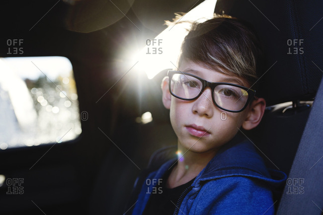 Kid with glasses sitting in back seat