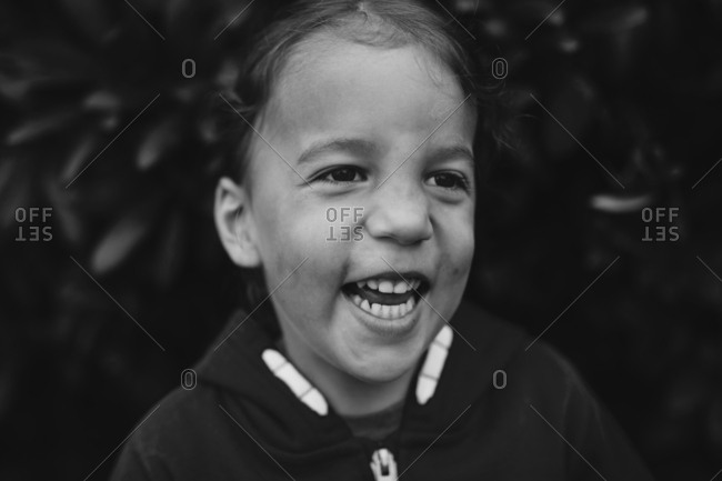 Boy laughing in front of shrubbery