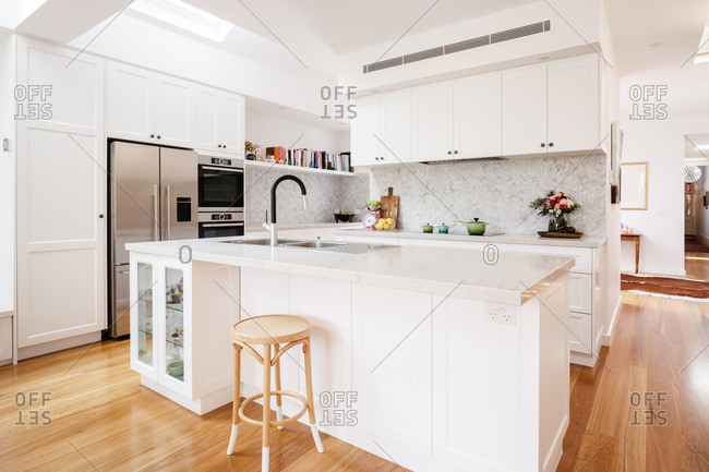 Stunning designer white kitchen renovation with large island counter top