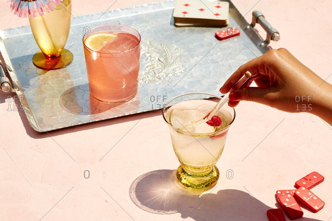Hand reaching for a summery cocktail outdoors on a pink surface