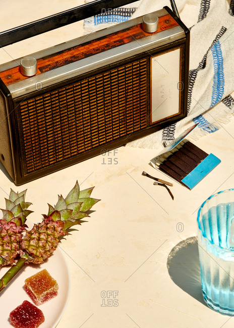 Vintage radio in the summer sun with beverage and snacks around