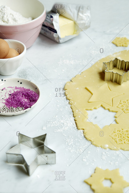 Cookie cutter sugar cookies being made with ingredients on marble counter