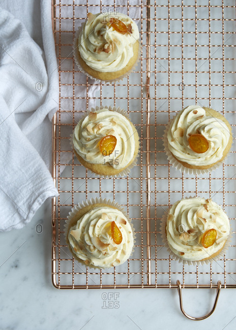 Batch of coconut kumquat cupcakes with cream cheese frosting resting on a baking rack from overhead