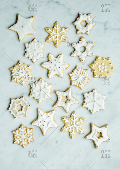 Fancy winter sugar cookies decorated with royal icing and sprinkles on a white marble surface