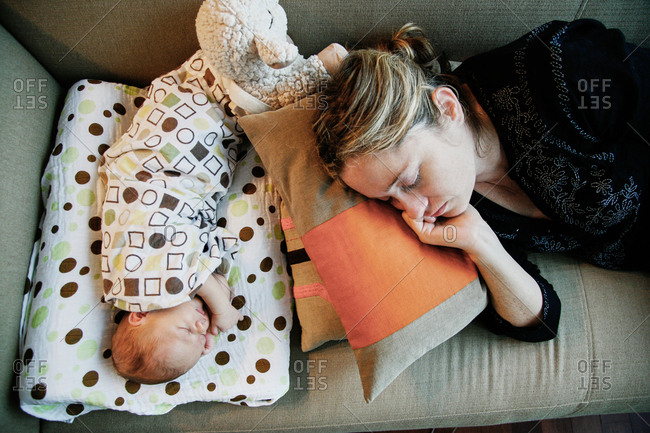 Baby and new born nap peacefully on sofa after retiring from hospital