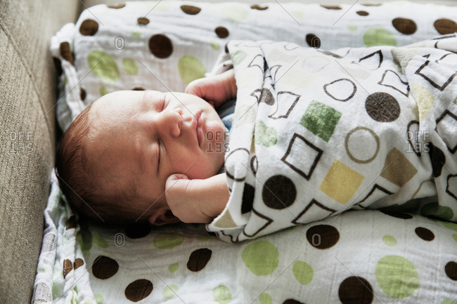 Baby swaddled in receiving blanket, sleeping soundly