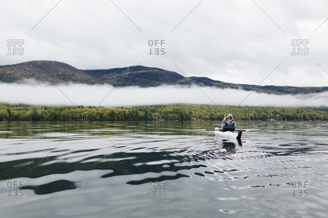 Woman photographing  landscape with cell phone while kayaking on Lake George, New York