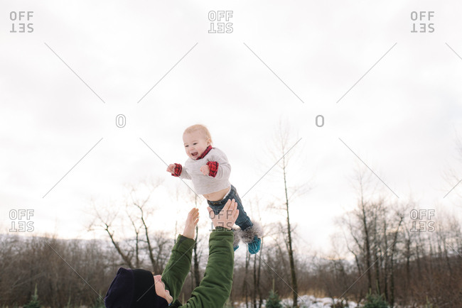 Father throws child into air on a winter day