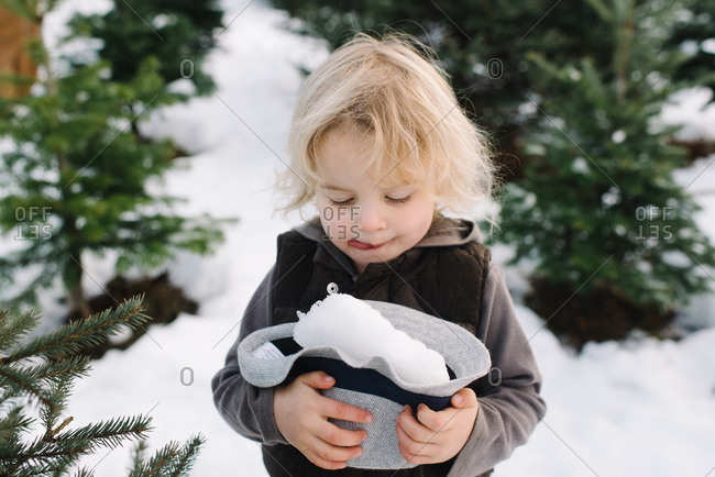Child with a hat full of snow at a tree farm