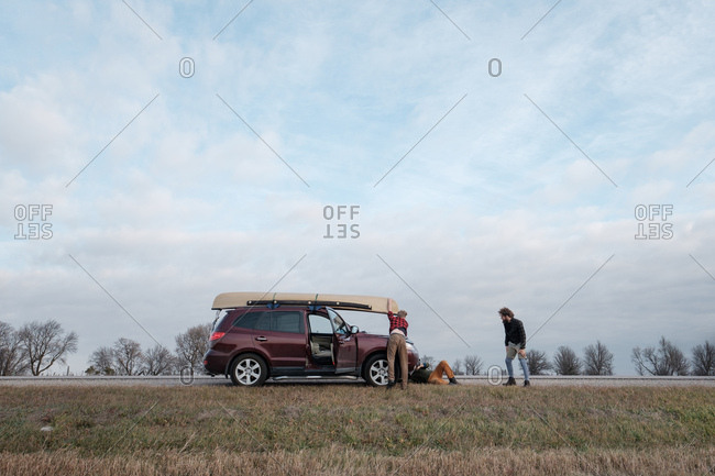 Adjusting a canoe mounted on car's rooftop on the side of a prairie road