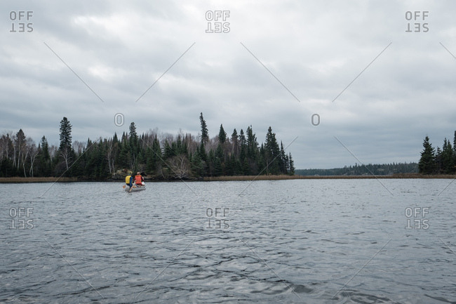 Paddling in a canoe on a remote lake under a cloudy fall sky