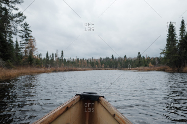View of remote lake from the bow of a canoe under cloudy fall sky