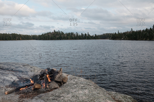 Small campfire burning next to calm remote lake under blue-grey fall sky
