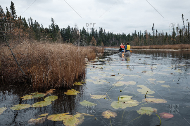 Paddling in a canoe through a marshy river under a cloudy fall sky