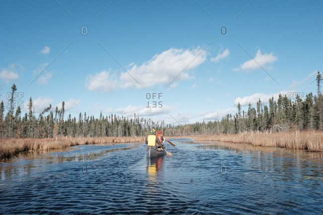 Paddling through marshy river under bright midday sun in fall