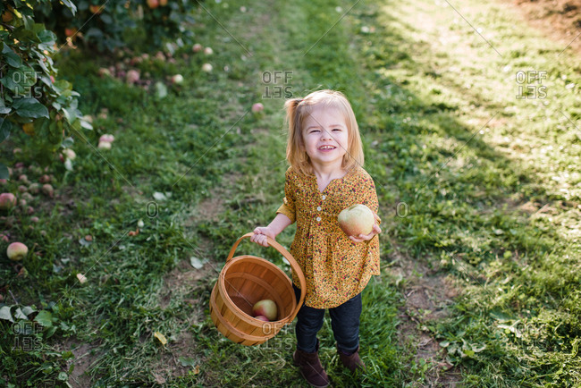 Girl holding a freshly picked apple and a basket