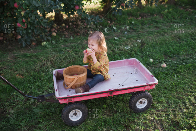 Girl sitting in a wagon eating an apple