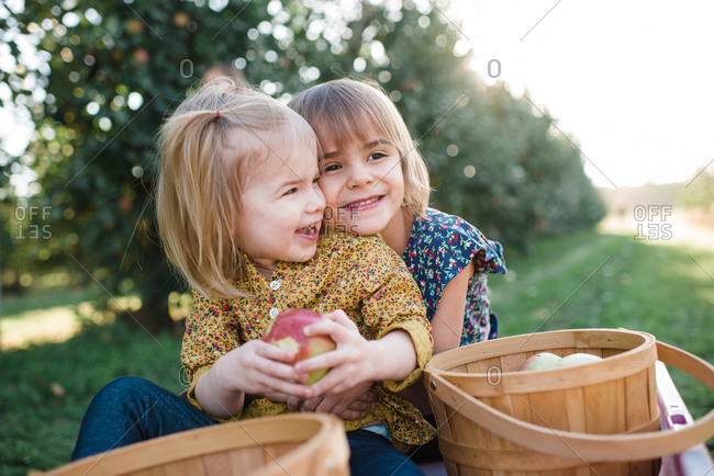Portrait of two sisters at apple orchard