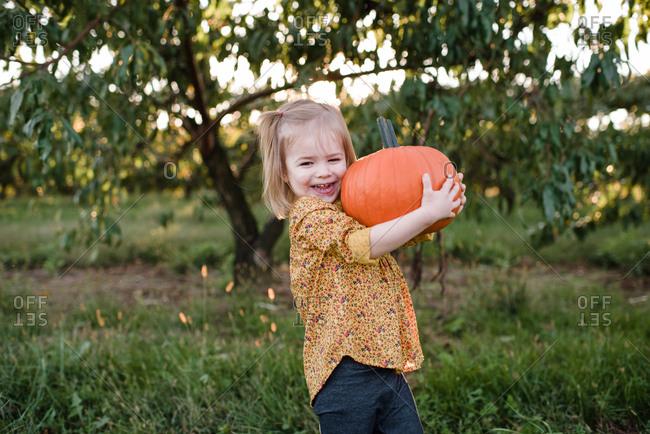 Smiling girl carrying a pumpkin