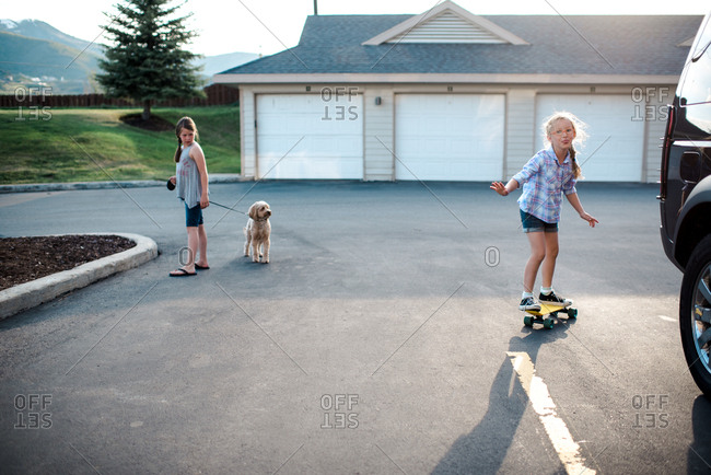 Girl riding on skateboard while her sister is walking the dog