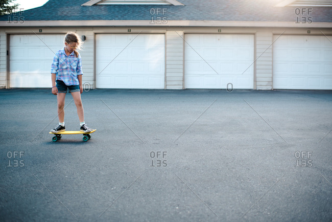 Girl riding a skateboard in neighborhood driveway
